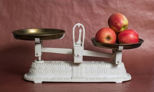A scale with apples on one side and nothing on the other side