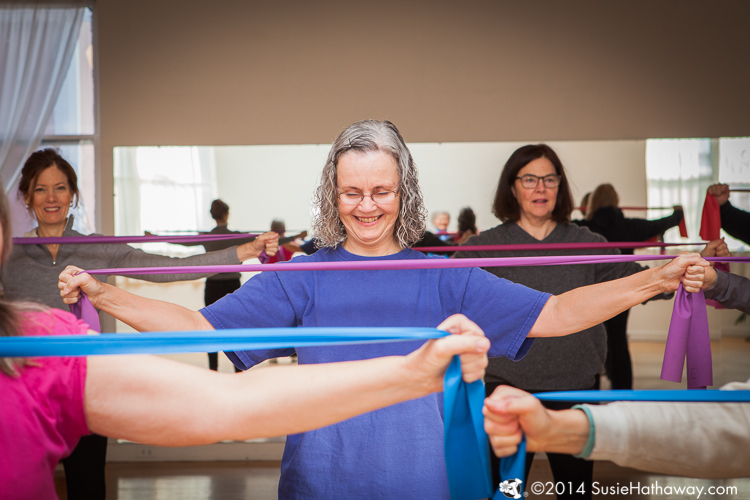 women with exercise bands across their chest