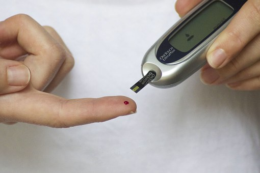 a finger with blood on it and a diabetes monitor near by
